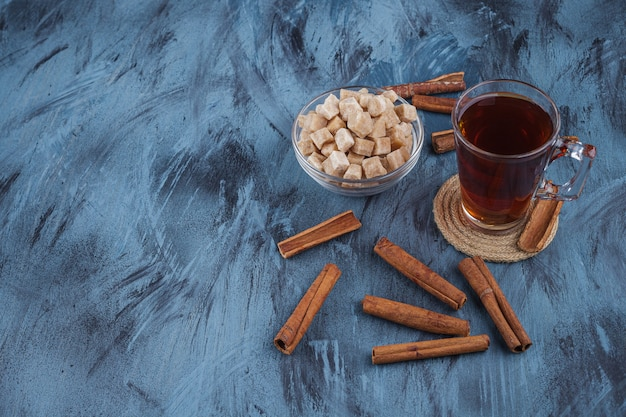Cup of black tea with bowl of brown sugar on blue background.