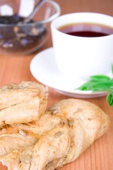 Cup of black tea with herbs and bread closeup