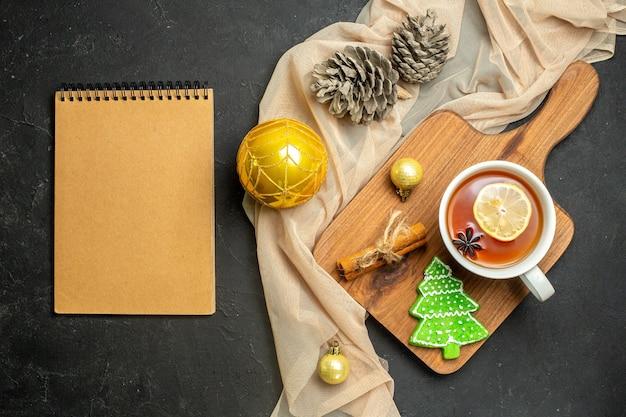 Una tazza di tè nero con accessori per la decorazione del nuovo anno al limone e cannella sul tagliere di legno