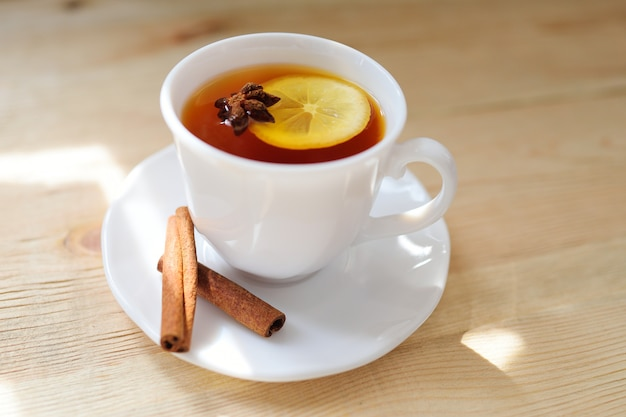 A cup of black tea with a lemon with cinnamon and a badan on a close-up table