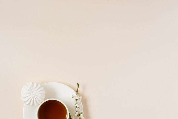Cup of black tea with marshmallows and spring flowers of apple tree on beige background with copy space