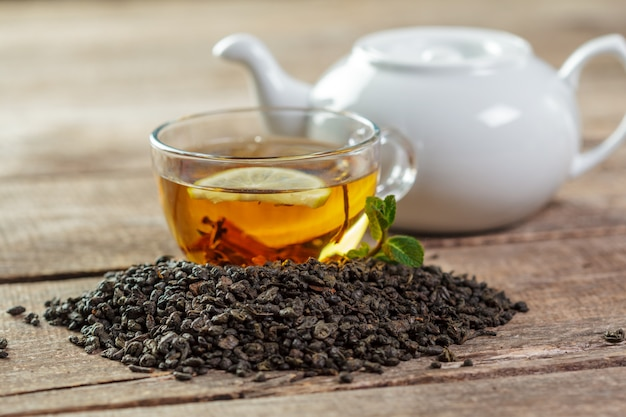 Cup of black tea with mint leaves on a wood