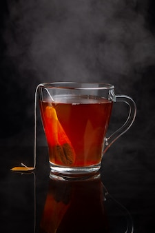 Cup of black tea with steam on a dark