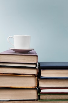 Cup on book stack with copy space
