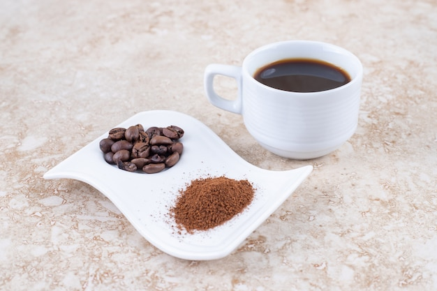 A cup of brewed coffee next to coffee beans and ground coffee powder on a fancy platter