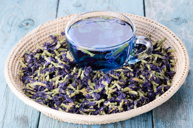 Cup of butterfly pea tea with blue dry flowers for healthy drinking