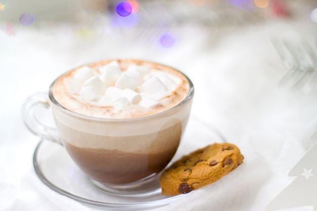 Cup of cacao hot chocolate with marshmallow and gingerbread cookies blurred lights