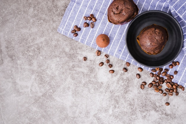 Cup cake and roasted coffee beans on napkin over the concrete background