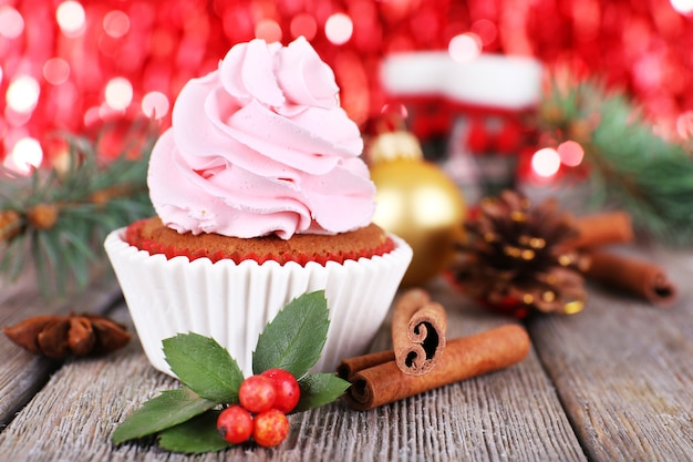 Торт с кремом и рождественским украшением на деревянном столе и ярко светит фон