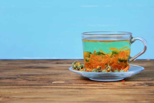 Cup of calendula tea on a wooden table on blue
