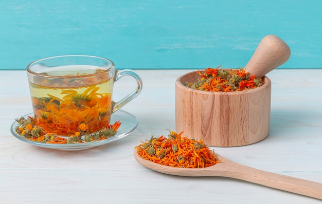 A cup of calendula tea on a wooden table, a mortar with calendula flowers