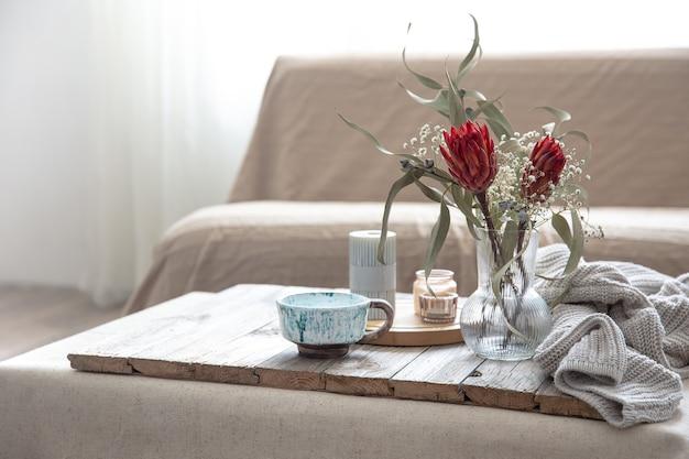 컵, 양초, 프로테아 꽃이 든 꽃병, 그리고 흐릿한 배경의 방에 있는 뜨개질 요소.