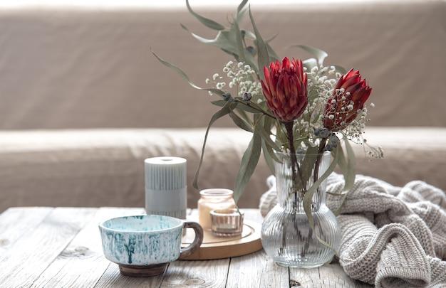 Tazza, candele, vaso con fiori di protea e un elemento a maglia nella stanza su uno sfondo sfocato.