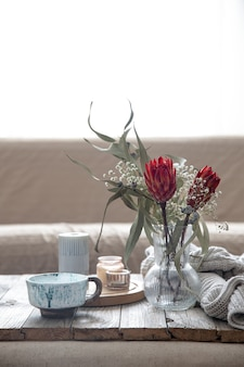 Cup, candles, vase with protea flowers and a knitted element in the room on a blurred background.
