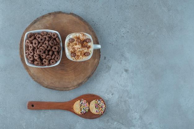 A cup of cappuccino and a bowl of corn ring on a board next to spoon, on the blue background.