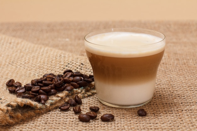 Cup of cappuccino, coffee beans and canvas sack on sackcloth background.
