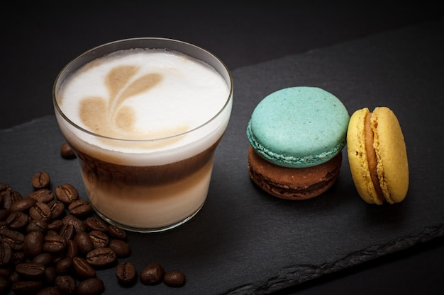 Cup of cappuccino, coffee beans and macaroons on black background. top view.
