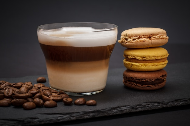 Cup of cappuccino, coffee beans and macaroons on black background.