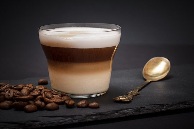 Cup of cappuccino, coffee beans and spoon on black background.