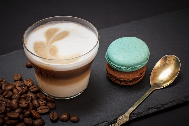 Cup of cappuccino, coffee beans, spoon and macaroons on black background. top view.