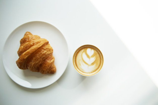 Cup of cappuccino coffee and croissant on white table, top view