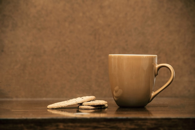 Cup of cappuccino coffee on dark table with cookies, colorful brown and clean