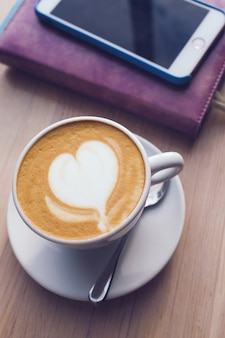 A cup of cappuccino coffee, a notebook and a phone are on a wooden table in the cafe.