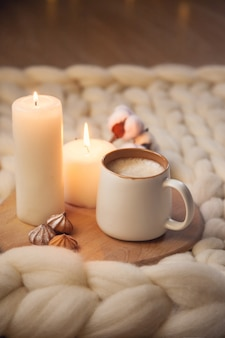 Cup of cappuccino, cookies, and candles on the background of blanket of thick yarn. the atmosphere of homeliness and comfort.