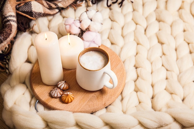 Cup of cappuccino and cookies, candles, checkered plaid on the background of blanket of thick yarn. the atmosphere of homeliness and comfort.