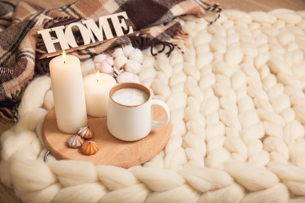 Cup of cappuccino and cookies, candles, checkered plaid, inscription home on the background of blanket of thick yarn. the atmosphere of homeliness and comfort.