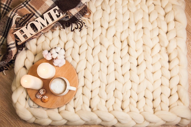Cup of cappuccino and cookies, candles, checkered plaid, inscription home on blanket of thick yarn. the atmosphere of homeliness and comfort. top view flat lay with copy space