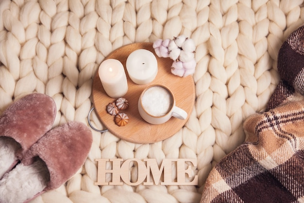 Cup of cappuccino, cookies, candles, cotton plant, home fur slippers, checkered plaid, inscription home on the blanket of thick yarn. the atmosphere of homeliness and comfort.