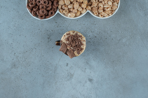 A cup of cappuccino next to cornflakes in a bowls , on the blue background.