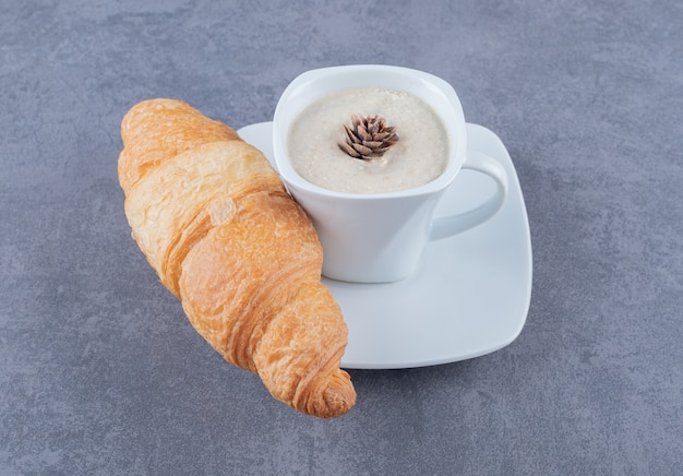 Cup of cappuccino and croissant for breakfast on grey background.