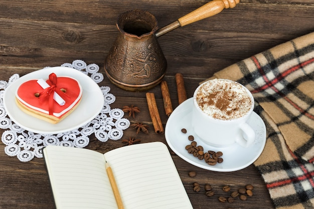 Cup of cappuccino, heart shaped cookies width message, notebook, pencil and coffee pots on a brown wooden table. holiday planning
