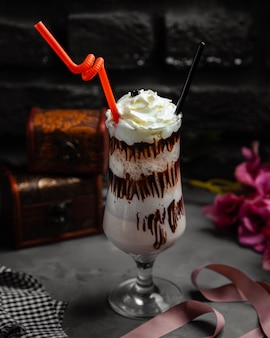 Cup of cappuccino milkshake with whipped cream and chocolate