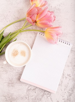 Cup of cappuccino, notebook and pink tulips top view on marble background