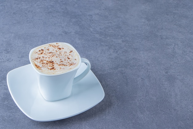 A cup of cappuccino on a saucer , on the blue background.