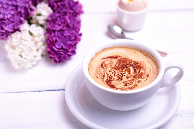 Cup of cappuccino on a white wooden table