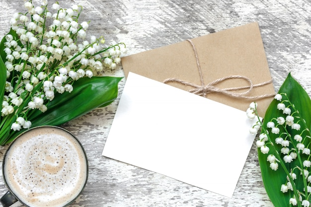 Cup of cappuccino with blank white greeting card and envelope with spring lily of the valley flowers