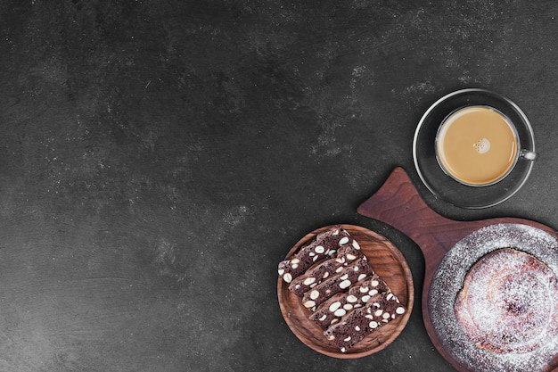 A cup of cappuccino with cocoa biscuit and sweet bun.