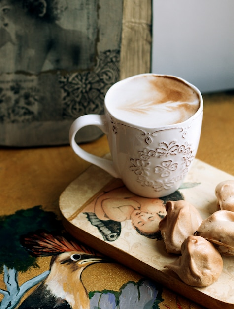 A cup of cappuccino with cookies