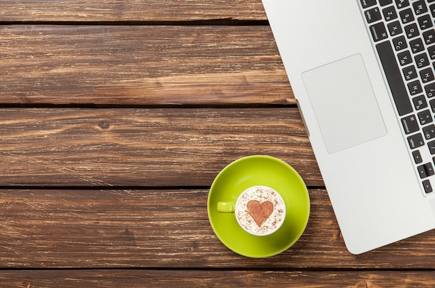 Cup of cappuccino with heart shape and laptop