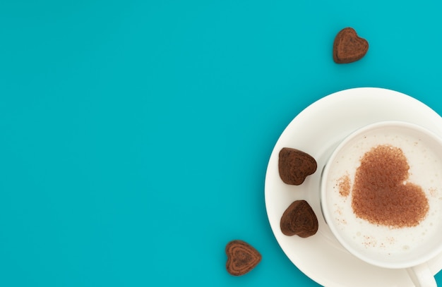 The cup of cappuccino with heart-shaped cocao on coffee foam and chocolate hearts on blue background