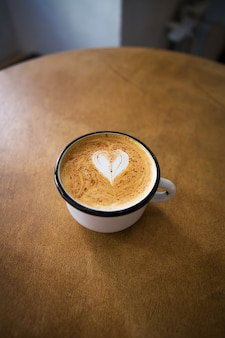 Cup of cappuccino with a heart shaped pattern on a wooden table