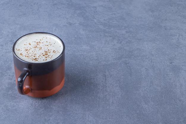 Una tazza di cappuccino con latte, sullo sfondo blu.