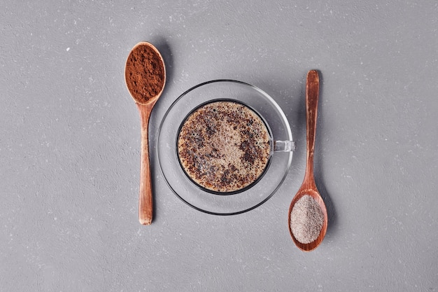 Una tazza di cappuccino con le polveri nei cucchiai.