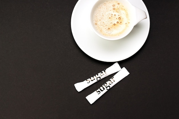 Cup of cappucino coffee with white sugar sachets on black table.