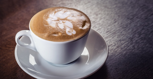 Cup of capuccino with rich decorative foam on top on a dark wooden table.