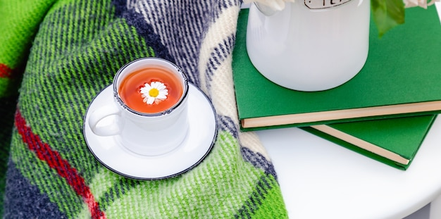 Cup of chamomile herbal tea with chamomile flower and teapot, books, warm plaid on white table outdoor. cozy home, nature background in garden. long web banner.